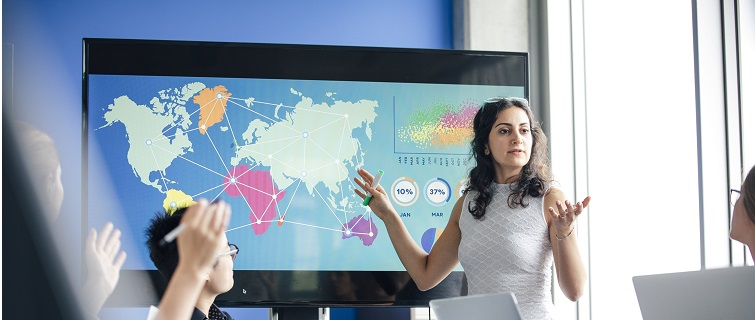 Woman pointing to map display in front of coworkers