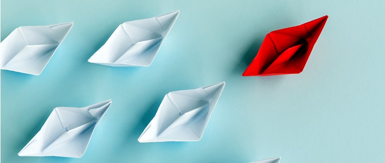 White origami boats following a red origami boat on blue background