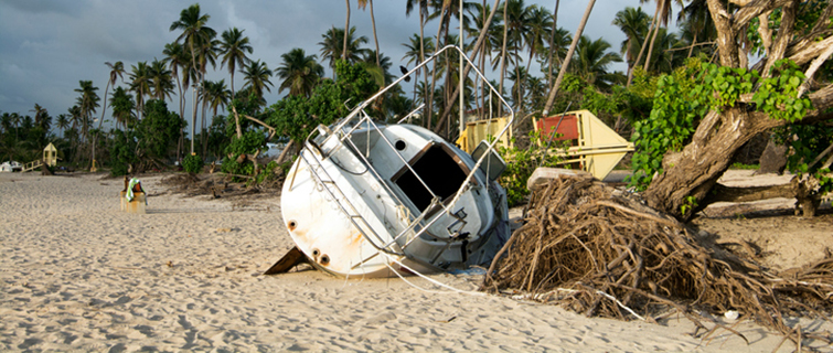 Boat damaged by hurricane aground on a beach