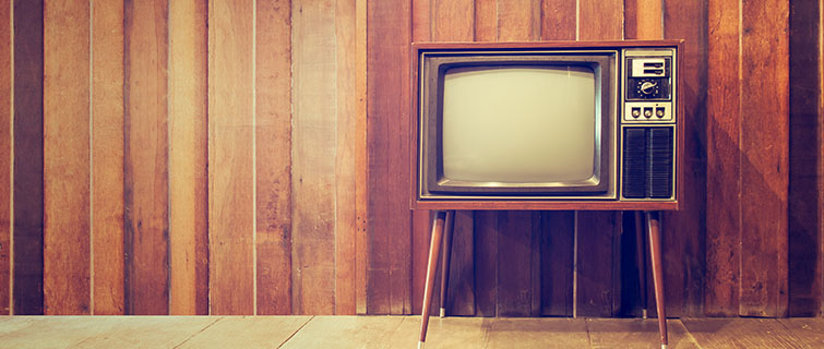 An old television sits in a paneled living room