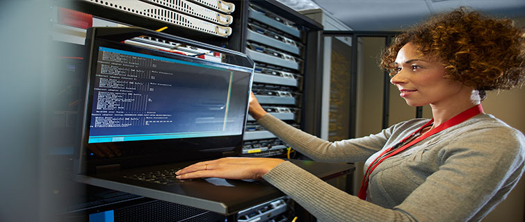 Woman standing next to a laptop and computer server