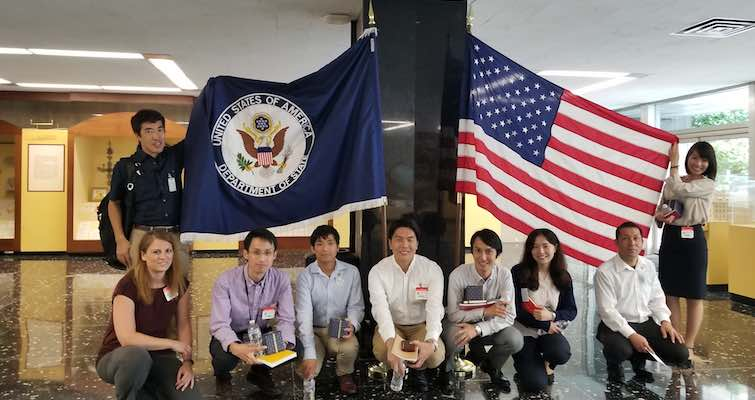 Group of students posing in front of US State Department and USA flags