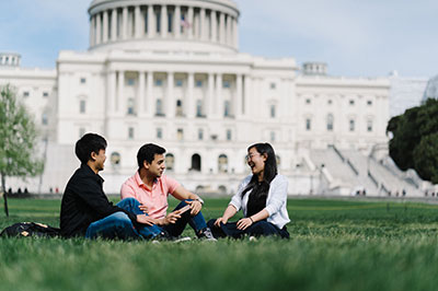 Three students on lawn outside of US capitol
