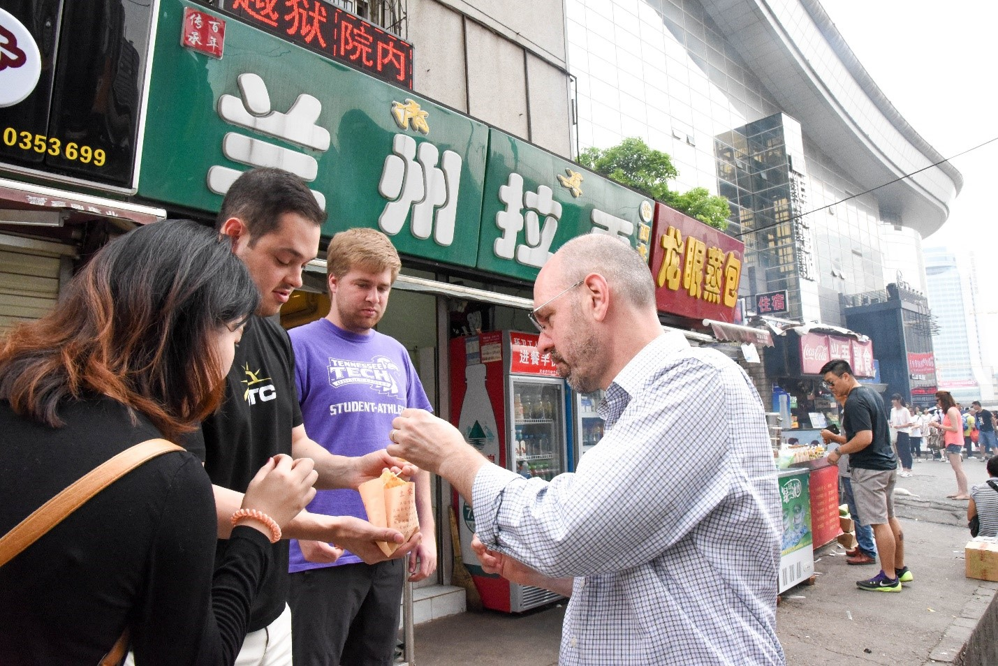 Uwe Brandes talking with students in front of a Wuhan Market